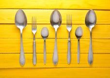 Ein Satz Löffel und Gabeln auf einem gelben Holztisch Lizenzfreies Stockfoto