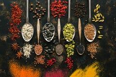 Ein Satz mannigfaltige Samen und Gewürze in den Löffeln auf einem dunklen Hintergrund Draufsicht, flache Lage Mehrfarbige Gewürze stockfoto