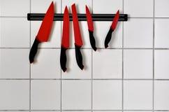 Ein Satz rote Messer, die an einer Küchenwand hängen Lizenzfreie Stockfotografie