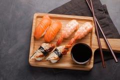 Ein Satz Sushi mit Lachsen, Garnele und Aal mit einer Schüssel Sojasoße und hölzernen Essstäbchen auf einem hölzernen Brett Köstl Lizenzfreie Stockbilder
