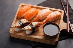 Ein Satz Sushi mit Lachsen, Garnele und Aal mit einer Schüssel Sojasoße und hölzernen Essstäbchen auf einem hölzernen Brett Köstl Lizenzfreies Stockfoto