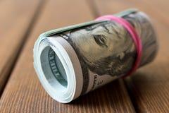 Ein Satz verdrehte 100 Dollarscheine Auf einer hölzernen Tabelle Abschluss oben Stockbild
