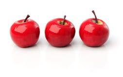 Ein Satz von drei roten Plastikäpfeln in Folge lizenzfreies stockbild