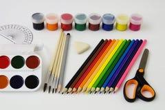 Ein Satz von farbigen Farben, von Bürste, von Bleistift, von Scheren und von Radiergummi Lizenzfreies Stockfoto
