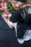 Ein Satz von Unterwäsche als Geschenk Schwarze Spitze Eine vertraute Überraschung an Valentinsgruß ` s Tag Blumenstrauß der rosaf lizenzfreie stockfotos