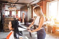 Ein schöner blonder Friseur stellt Frisur ihr Haar zu ihrem Kunden in einem stilvollen Schönheitssalon her Stockbild