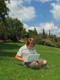 Ein schöner blonder Junge spielt auf dem Laptop Lizenzfreies Stockbild