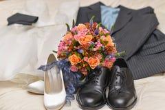 Ein schöner Blumenstrauß ist auf Schuhen der Braut und des Bräutigams und nahe bei ihrer Kleidung stockbild