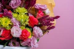 Ein schöner Blumenstrauß von rosa eustoms, eine gelbe Chrysantheme, eine rote und rosa Rose, auf einem rosa Hintergrund Stockbild