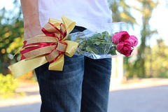 Ein schöner Blumenstrauß von roten Rosen mit Band wird vom jungen Mann mit weißem Hemd auf Natur unscharfem Hintergrund gehalten  Lizenzfreies Stockfoto