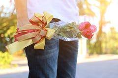 Ein schöner Blumenstrauß von roten Rosen mit Band wird vom jungen Mann mit weißem Hemd mit Sonnenscheineffekt auf Natur unscharfe Stockfotografie