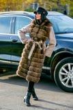 Ein schöner Brunette in einem hellen Mantel mit Pelz, schwarzer Hose und einer schwarzen Kappe steht nahe einem Auto an einem son lizenzfreie stockbilder