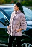 Ein schöner Brunette in einem hellen Mantel und schwarzen einer Hose des Pelzes steht nahe einem Auto an einem sonnigen Tag des H lizenzfreie stockfotos