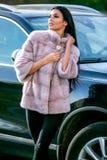 Ein schöner Brunette in einem hellfarbigen Mantel und schwarzen einer Hose des Pelzes steht nahe einem Auto an einem sonnigen Tag stockfotografie