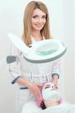 Ein schöner Damenkosmetiker macht ihrem Kunden im Schönheitssalon eine Gesichtsmaske lizenzfreies stockfoto