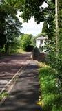 Ein schöner englischer Landschaftsweg mit weißem Haus und Steinwand Stockbilder