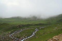 Ein schöner Hügel, ein Bach und Wolken lizenzfreie stockbilder