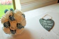 Ein schöner heller Brautrosen-Blumenstrauß mit Schiefer neue Herr und die Frau heart Stockfotos