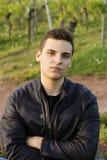 Ein schöner junger überzeugter Mann in einer Lederjacke sitzt nahe bei den Hügeln der Trauben stockfotos