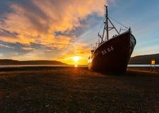Ein schöner Schuss eines Fischerbootes, das dem Strand bei Sonnenaufgang sich nähert stockfotografie