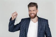 Ein schöner sexy bärtiger Geschäftsmann in einer Jacke betrachtet der Kamera glücklich und hält die Schlüssel in seiner Hand er k stockfotos