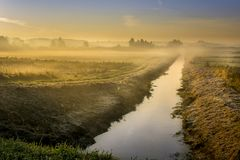 Ein schöner Sonnenaufgang über einer nebelhaften Wiese und einem Fluss stockfotos