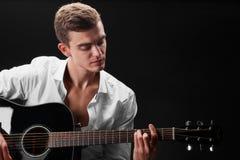 Ein schöner und Erfolgsmann, der Gitarre spielt und Lieder auf einem schwarzen Hintergrund singt Musik, Lieder, Rock, Popkonzept Stockbilder