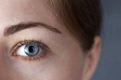 Ein schöner weiblicher Abschluss des blauen Auges oben lizenzfreies stockbild