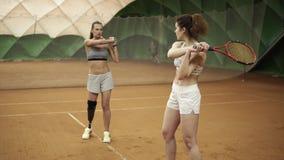 Ein schönes, athletisches ungültiges Mädchen unterrichtet den Anfänger der korrekten Flugbahn eines Schlägers, der im Tennis gesc stock video footage