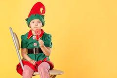 Ein schönes Baby in einer Klage einer Weihnachtselfe sitzt auf einem Stuhl Sie hat einen köstlichen Lutscher in ihren Händen Über lizenzfreies stockfoto