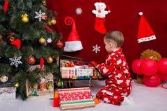 Ein schönes Baby setzt Weihnachtsgeschenke Stockbilder