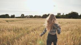 Ein schönes blondes jugendlich Mädchen läuft über ein Weizenfeld und dreht sich herum und lächelt stock video