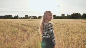 Ein schönes blondes jugendlich Mädchen steht auf einem Weizengebiet mit ihr sich drehte zurück und Lächeln stock footage