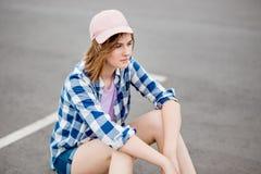 Ein schönes blondes Mädchen, das karierte Hemd-, Kappen- und Denimkurze hosen trägt, sitzt auf dem Parkplatz mit einem durchdacht stockfotografie