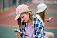 Ein schönes blondes Mädchen, das kariertes Hemd und eine Kappe trägt, sitzt auf dem Sportfeld mit einem Telefon in ihrer Hand spo lizenzfreie stockfotografie