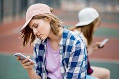 Ein schönes blondes Mädchen, das kariertes Hemd und eine Kappe trägt, sitzt auf dem Sportfeld mit einem Telefon in ihrer Hand spo lizenzfreies stockbild