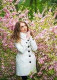Ein schönes blondes Mädchen in einem weißen Mantel ist, träumend aufwerfend und im Garten von Kirschblüten stockfotos