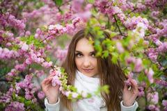 Ein schönes blondes Mädchen mit grünen Augen in einem weißen Mantel und in einem weißen Schal steht im Wald in einer rosa Kirschb stockbilder