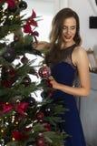 Ein schönes dünnes lächelndes Mädchen, das in einem langen Glättungskleid gekleidet wird, schmückt den Weihnachtsbaum in einem fe lizenzfreie stockfotos