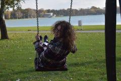 Ein schönes glückliches junges Mädchen auf einem Schwingen im Park Stockbilder