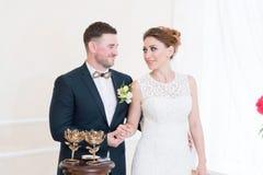Ein schönes glückliches Paar im Registeramt führt ein Hochzeitsritual mit Kerzenbeleuchtung durch Stockfotografie