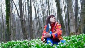 Ein schönes intelligentes Mädchen liest ein interessantes Buch in einem Frühlingswald voll von blühenden Schneeglöckchen stock video