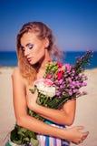 Ein schönes junges blondes Mädchen, das auf dem Strand aufwirft Lizenzfreie Stockfotografie