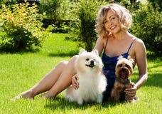 Ein schönes junges blondes Mädchen im Park mit Hunden lizenzfreies stockfoto