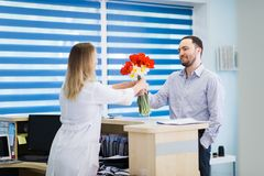 Ein schönes junges Mädchen in einem weißen Mantel steht nahe dem Schreibtisch im Büro und nimmt boquet von Blumen von lizenzfreie stockfotos