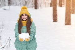 Ein schönes junges Mädchen in einer Strickmütze hält Schnee in ihren Händen, vor dem hintergrund eines Winterwaldes stockbilder