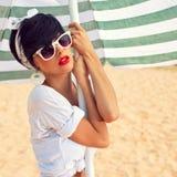 Ein schönes junges Mädchen im Retro- Blick mit den roten Lippen in einem weißen Schalter Stockfotos