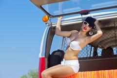 Ein schönes junges Mädchen im Retro Blick mit einem weißen Badeanzug, ein Ba Stockfotografie