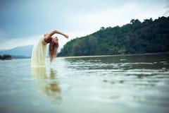 Ein schönes junges Mädchen im weißen Kleid verbog in wate Stockfotografie
