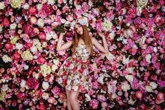 Ein schönes junges Mädchen mit Blumenblumenstrauß nahe einer Blumenwand Lizenzfreies Stockfoto